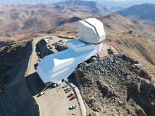 Photo of Rubin Observatory taken from above by a drone. The observatory has a white dome and a long support building that extends to the left of the dome. The observatory is on a dry, brown mountain top with other mountains stretching into the distance.